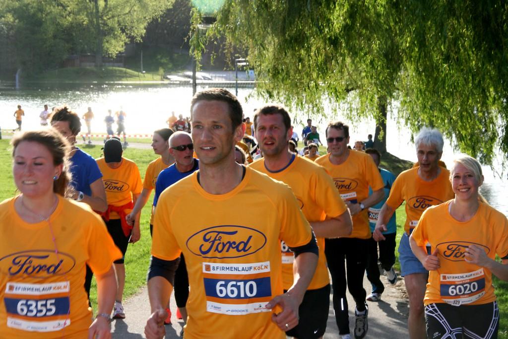 Laufen ohne Wettkampfstress: 7012 Läufer und Walker gingen bein 8. Firmenlauf Köln auf die sechs Kilometer lange Laufstrecke am Fühlinger See. Viele trugen T-Shirts mit dem Namen und Logo ihres Unternehmens.